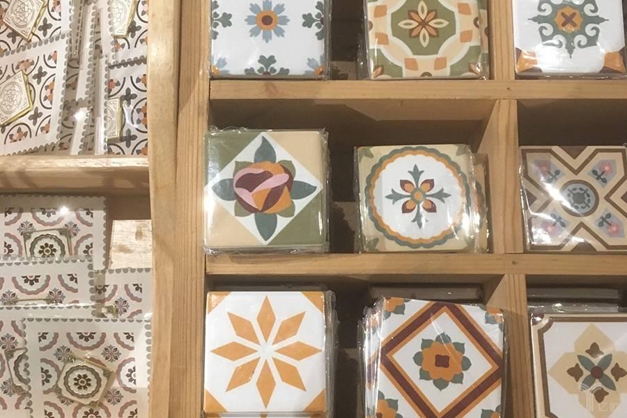 陈列在收银台附近的冰箱贴、徽章等花砖衍生品。